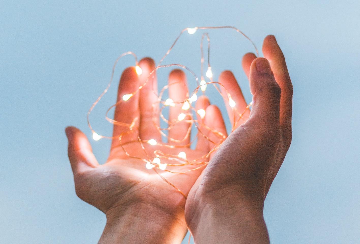 Offene Hände mit Lichterkette